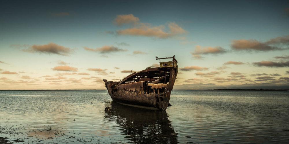 Wandbild einsames Schiffsfrack Strand Sonnenuntergang